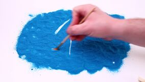 Man hand writing number one on a blue art sand. Studio footage on a white background.