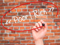 Man Hand writing Poor - Rich with black marker on visual screen. Isolated on background. Business, technology, internet concept. Stock Photo royalty free stock images