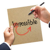 Man hand writing possible from impossible. Motivation concept. On his paper Stock Images