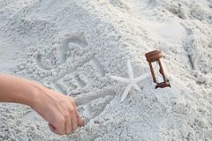 Man hand writing sea word on sand with shell Royalty Free Stock Photo