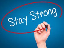 Man Hand writing Stay Strong with black marker on visual screen. Stock Image