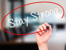 Man Hand writing Stay Strong with black marker on visual screen. Stock Photography