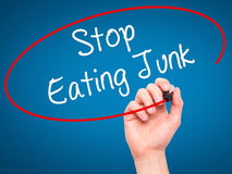 Man Hand writing Stop Eating Junk with black marker on visual sc Stock Image
