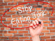 Man Hand writing Stop Eating Junk with black marker on visual sc Royalty Free Stock Images