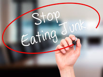 Man Hand writing Stop Eating Junk with black marker on visual sc Stock Photos