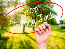 Man Hand writing Stop Eating Junk with black marker on visual sc Royalty Free Stock Photography