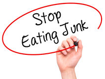 Man Hand writing Stop Eating Junk with black marker on visual sc Royalty Free Stock Photos