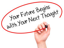 Man Hand writing Your Future Begins With Your Next Thought with Stock Photography