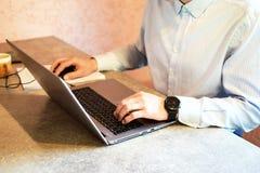 Man handarbete med bärbara datorn på grå färgtabellen royaltyfria bilder