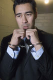 Man In Handcuffs. Depressed businessman with handcuffs in prison cell Royalty Free Stock Photography