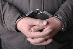Man with handcuffs. Detail of the hands of a arrested man, with handcuffs Royalty Free Stock Photography