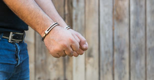 Man with Handcuffs. Arrest, close-up shot man's hands with handcuffs in front of plank wood wall with copy-space Royalty Free Stock Images