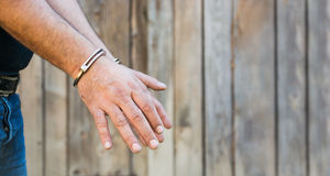 Man with Handcuffs. Arrest, close-up shot man's hands with handcuffs in front of plank wood  wall with copy-space Stock Image