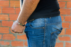 Man with Handcuffs. Arrest, close-up shot man's hands with handcuffs in front of terracotta brick blocks wall, left hand side Royalty Free Stock Images