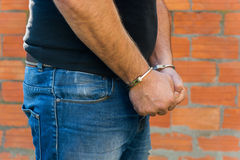 Man with Handcuffs. Arrest, close-up shot man's hands with handcuffs in front of terracotta brick blocks wall, right hand side Royalty Free Stock Photos