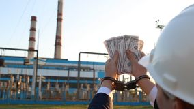 A man in handcuffs counts money dollars against a power plant background, sunset, close-up. Arrest, handcuffs stock footage