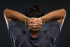 Man in handcuffs on gray background. Man in handcuffs with hands on neck on gray background Stock Photography