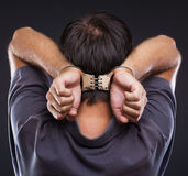 Man in handcuffs on gray background. Man in handcuffs with hands on neck on gray background Stock Image