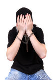 Man in Handcuffs Hide his Face. Young Man in Handcuffs hide his Face Isolated on the White Background Stock Images