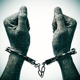 Man with handcuffs in his wrists. Closeup of a handcuffed man with his hands and wrists patterned with no-sense words Royalty Free Stock Images