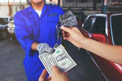Man handed the money to Car mechanic holding in a hand car keys stock photo