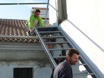 Man handeling steel staircase. Alora, Spain - December 15, 2011: Men lifting steel staircase into position in village house, Andalusia Royalty Free Stock Images