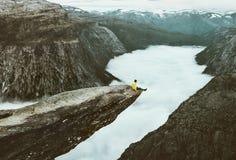 Man handelsresanden på Trolltunga den steniga klippkanten i Norge royaltyfria bilder