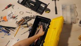 Man handen assembleert hulpmiddelen in een doos stock videobeelden