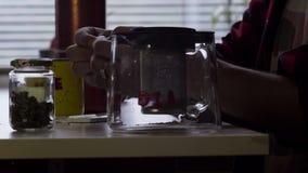 Man handen maken gerolde sigaret bij lijst met mok en glastheepot in keuken stock video