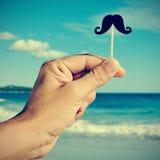 Man handen med en fejkamustasch på stranden, med en filtereffekt Arkivfoto