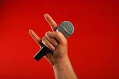 Man handen med mikrofon- och jäkelhorn över rött Royaltyfri Foto