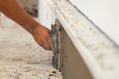 Man handen med mursleven som rappar ett fundament av huset arkivfoton