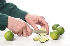 Man handen met een mes snijden kalkfruit op een marmeren lijst met exemplaarruimte voor uw tekst stock fotografie