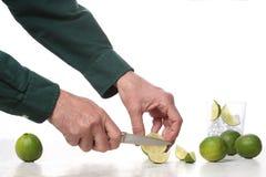 Man handen met een mes snijden kalkfruit op een marmeren lijst met exemplaarruimte voor uw tekst royalty-vrije stock foto