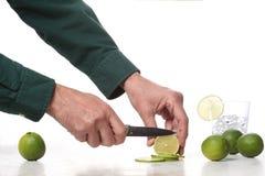 Man handen met een mes snijden kalkfruit op een marmeren lijst met exemplaarruimte voor uw tekst royalty-vrije stock fotografie