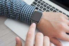Man handen som rymmer en klocka på bakgrunden av bärbara datorn Royaltyfri Bild