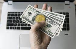 Man handen som rymmer ett guld- mynt av bitcoin med oss dollarräkningen mot en bärbar dator på bakgrunden Bitcoin är ett crypto Royaltyfri Fotografi
