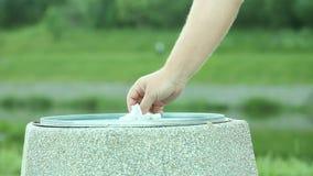 Man handen som ut kastar stycket av papper i soptunna arkivfilmer