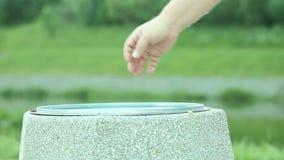 Man handen som ut kastar stycket av papper i soptunna stock video