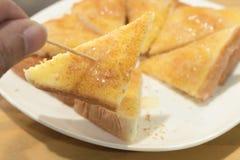 Man handen som väljer upp rostade brödet Arkivfoton