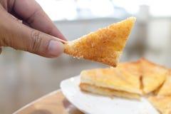 Man handen som väljer upp rostade brödet Fotografering för Bildbyråer