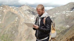 Man handen wat betreft het scherm van digitale tablet op de achtergrond van bergen stock videobeelden