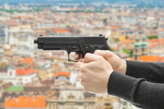 Man with a handgun ready to shoot - focus on handgun and blurred scenery of city on background Stock Image