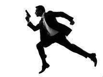 Man with handgun running silhouette. One caucasian man running with handgun in silhouette on white background royalty free stock photos