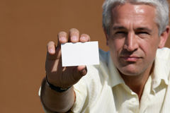 Man handing blank business card. Portrait of businessman handing blank business card Royalty Free Stock Photography