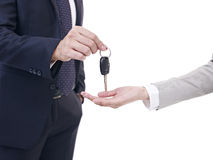 Man handing car key to woman. Close-up of male's hand handing car key to female's hand, isolated on white Stock Photos