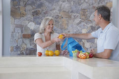 Man Handing Fruit To Woman At Kitchen Counter Stock Photos