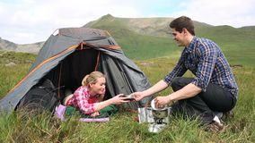 Man handing his girlfriend a bowl of soup on a camping trip. In the countryside stock video