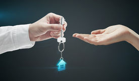 Man is handing a house key to a woman Stock Photo