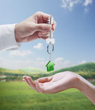 Man is handing a house key to a woman. Stock Image